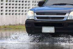Car splashes through a large puddle on a flooded street Royalty Free Stock Images