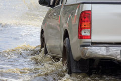 Car splashes through a large puddle on a flooded street. In Bangpoo Industrial Estate Royalty Free Stock Image