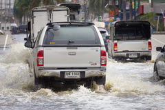 Car splashes through a large puddle on a flooded street. Samut Prakan, Thailand  August 27, 2014: There was flooding on the street near the market in Bang Pu Royalty Free Stock Image
