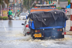 Car splashes through a large puddle on a flooded street. Samut Prakan, Thailand August 27, 2014: There was flooding on the street near the market in Bang Pu Royalty Free Stock Photography