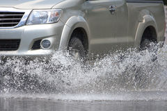 Car splashes through a large puddle on a flooded street. In thailand Royalty Free Stock Photos