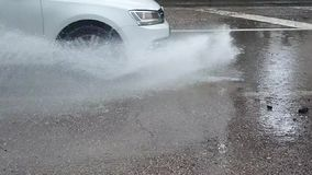 A car splashing water from a puddle of water stock video