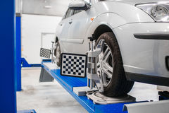 Car on stand with sensors wheels for alignment camber check in workshop of Service station. Royalty Free Stock Photos