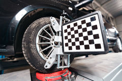 Car on stand with sensors wheels for alignment camber check in workshop of Service station. Stock Photos