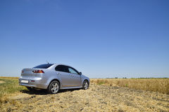 The car, standing on the edge of a wheat field. Rest and relaxation in nature. The desire to find solitude. Royalty Free Stock Image