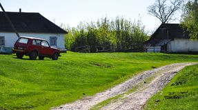 Car standing on green grass near rural buildings. For your design Royalty Free Stock Photo