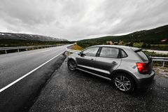 Grey modern car is parking next to a rural paved road which leads through the nature of Norway as far as the eye can see. The car is standing on the right side Stock Photo
