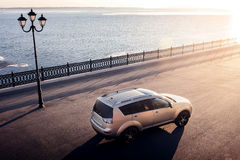 Car stay on embankment in city near river and lantern at sunset Stock Photos