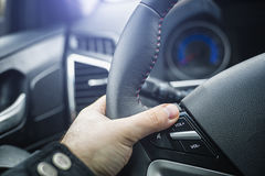 Car steering wheel with audio control buttons. Car steering wheel with buttons for controlling audio and human hand with shallow depth of field royalty free stock image