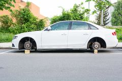 Car with stolen wheels. White vehicle left on wooden bricks Royalty Free Stock Photo