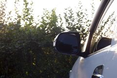 Car stop on garden. Car stop on garden view on mirror beside of car Royalty Free Stock Photo
