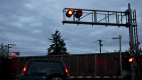 Car stopped at railway level crossing barriers and flashing lights for train. Motion of car stopped at railway level crossing barriers and flashing lights for stock video footage