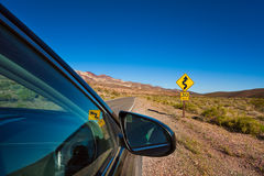 Car stopped on the road with arrow yellow sign. In desert, California, United States Stock Photos
