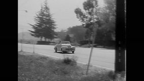Car stopping by broken down police car on road, 1950s stock footage
