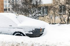 Car on a street covered with big snow layer. Royalty Free Stock Image