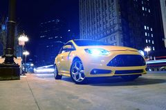 Car on the Street at Night. Sporty Car on the Street at Night. Agressive Looking Sporty Yellow Car on the Street of Chicago. Transportation Photo Collection Royalty Free Stock Photo