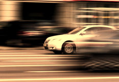 Car street traffic motion. Urban traffic motion concept: a white car going with a high speed along street with marking on the asphalt Stock Photos