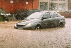 Car stuck in flash flood disaster. Unidentifiable passengers stuck in a car during heavy rains and flash flood - insurance claim concept Royalty Free Stock Photography