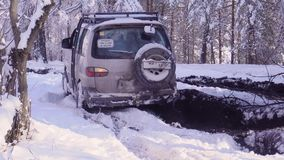 Car stuck in the mud in the winter forest, 4k. Car stuck in the mud in the winter forest stock video footage