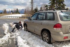 Car is stuck in snow in the mountains on a lonesome road. ADYGEA, RUSSIA, 05 MAY 2015: Car is stuck in snow in the mountains on a lonesome road stock photos