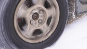 The wheel is slipping in the snow. Car stuck in the snow. Snow element. Drivers can not get out of the snow stock video