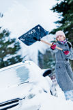 Car Stuck in the snow and a Woman Shoveling Stock Photography