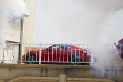Car stunt performance. Professional stunt car performing, passing through fire and smoke on bridge Stock Images