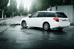 Car Subaru Legacy stay on asphalt road and reflected in puddle in the city at daytime Royalty Free Stock Photo