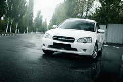 Car Subaru Legacy stay on asphalt road and reflected in puddle in the city at daytime Royalty Free Stock Photography