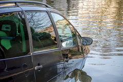 Car submerged in flood water. Car partially submerged in flood water on flooded road stock photography