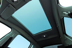 Car sunroof. Photo large sunroof inside car, sky and clouds Royalty Free Stock Images