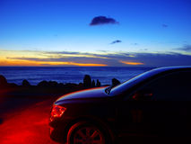 Car and sunset. In seacoast Royalty Free Stock Photography