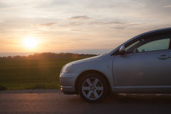 Car at sunset. The car on a background of sunset and green field royalty free stock photo