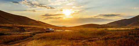 Car at sunset. Fantastic orange sky with cumulus clouds. Beauty world Royalty Free Stock Photo