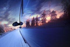 Car at sunset in winter road Royalty Free Stock Photography