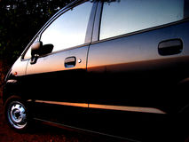 Car Sunsets. The sunset in tropical India reflected on a black car Stock Photo