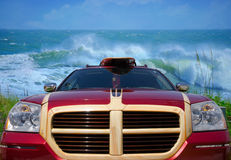 Car with surfboard at beach with big waves Royalty Free Stock Photo