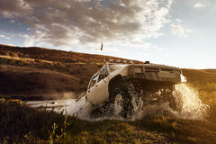 Car SUV overcomes water on the offroad background. Car SUV overcomes water on the offroad and sky background stock images
