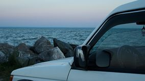 Car SUV white against the evening sea and a pile of large stones close-up stock video footage