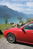 Car in swiss mountains. Red car in swiss mountains near beautiful blue lake, between Meiringen and Interlaken in Switzerland stock photos