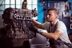 Car technician maintaining automotive engine. Photo of uniformed car technician maintaining automotive engine stock images