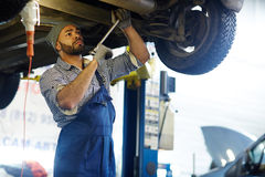 Car technician. Troubleshooting master with hand-tool repairing car Royalty Free Stock Photo