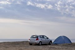 Car and a tent against the background of the sea. Royalty Free Stock Photography