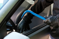 Car theft. Man is a black mask trying to steal a parking car at daytime royalty free stock photography