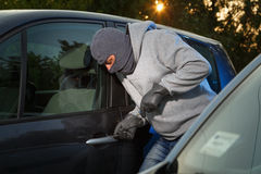 Car theft. Robber breaking into a car with a screwdriver royalty free stock photo