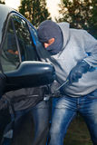 Car theft. Car thief breaking into a car on the parking lot royalty free stock photos