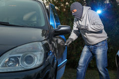 Car theft. Car thief breaking into a car on the parking lot and opening the door Royalty Free Stock Photo