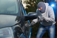 Car theft. Car thief breaking into a car on the parking lot with a screwdriver Royalty Free Stock Photography