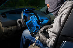 Car theft. Car thief breaking into a car and starting it with a lap top Stock Photography