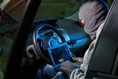 Car theft. Car thief hacking into the car computer Stock Image